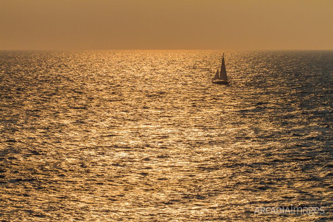 A sailboat sailing close to Cape Maleas during sunrise, Laconia, Peloponnese