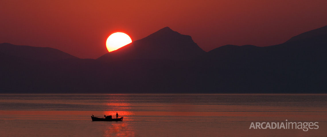 A fishing boat at sunrise at the Argolic gulf close to Astros Kynourias, Arcadia, Greece