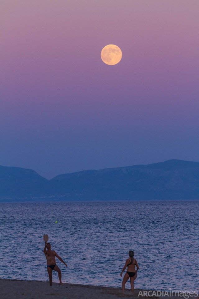 A couple playing beach tennis after sunset, Mavrovouni beach, Laconia, Peloponnese, Greece
