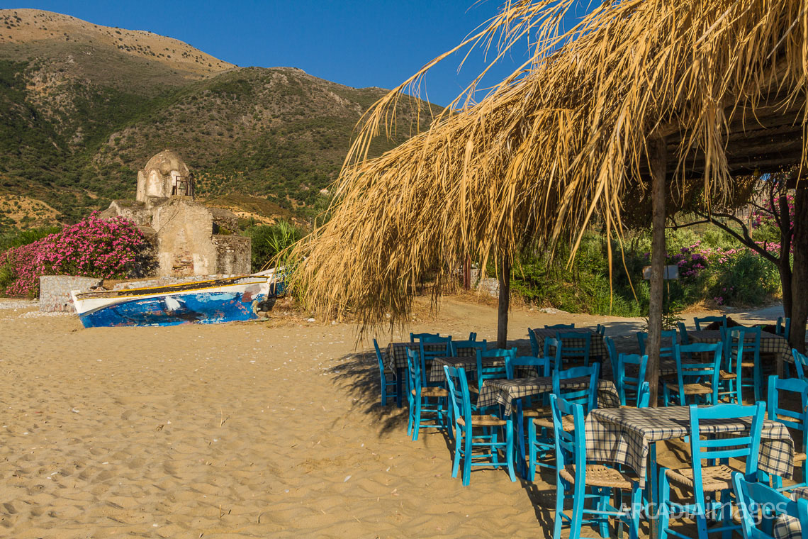 The chairs of a beach fish-tavern and the Byzantine church of Aghia Varvara in the background. Skoutari, Laconia, Peloponnese
