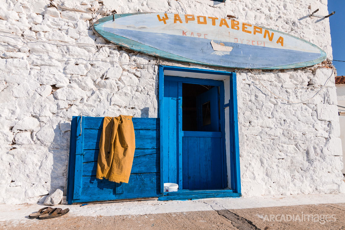 The entrance of a fish tavern with its sign, the fishermans pants and sandals. Aghia Varvara beach, Skoutari, Laconia, Peloponnese