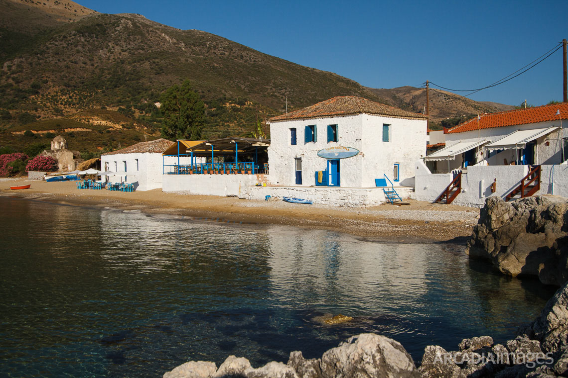 Aghia Varvara beach, a fish-tavern and the Byzantine church of Agia Varvara in the background. Skoutari, Laconia, Peloponnese