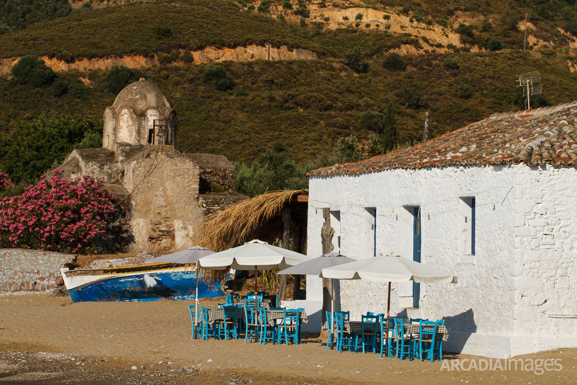 The chairs of a fish tavern and the Byzantine church of Aghia Varvara in the background. Skoutari, Laconia, Peloponnese