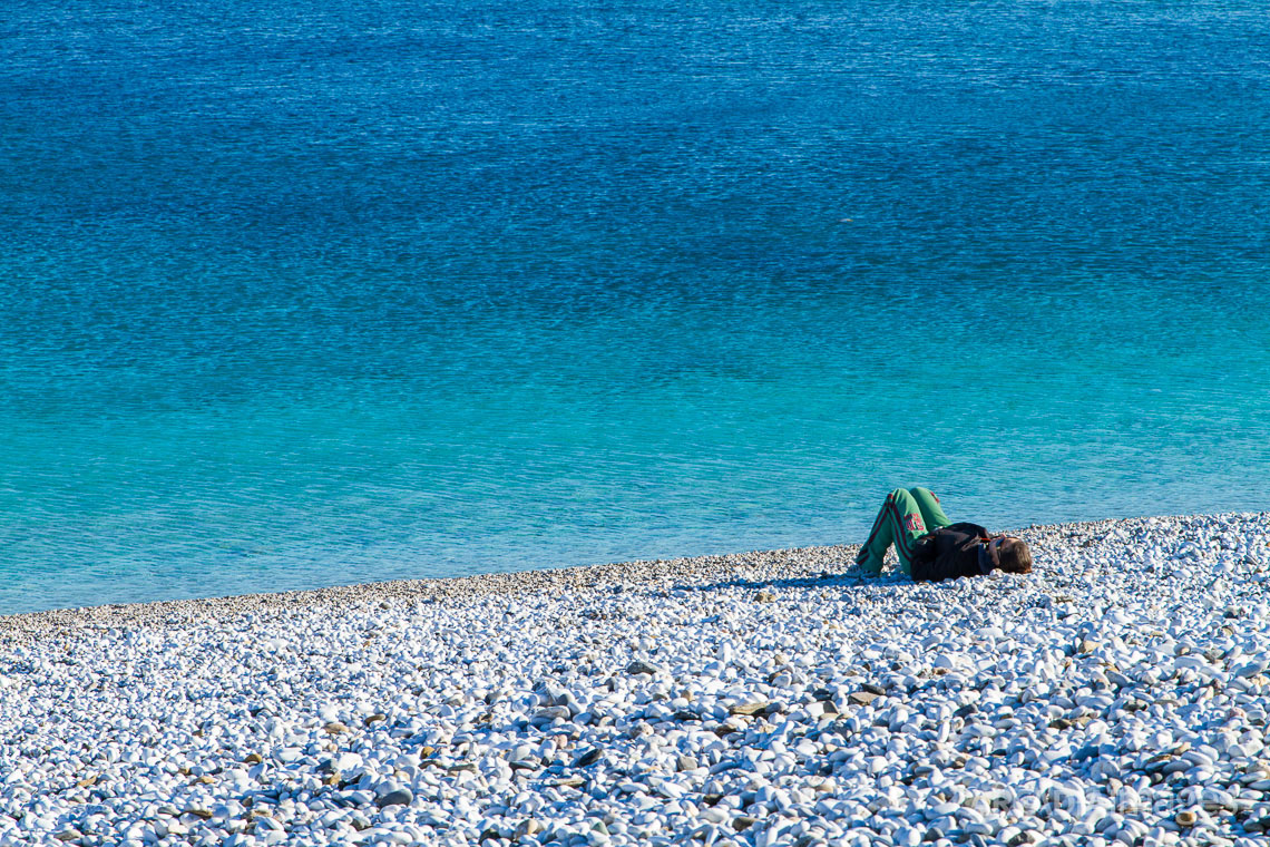 A woman enjoys the sun at Halikia-Vata pebble beach. Kotronas, Mani, Peloponnese, Greece
